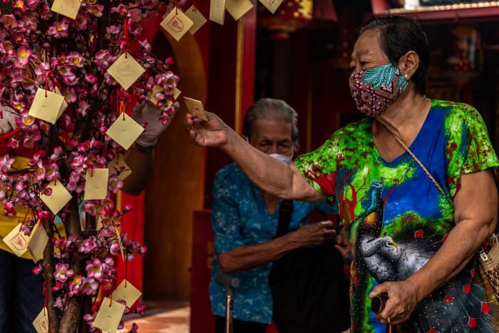 Warga lanjut usia (lansia) memilih kertas pada pohon doa dan harapan usai menerima angpau