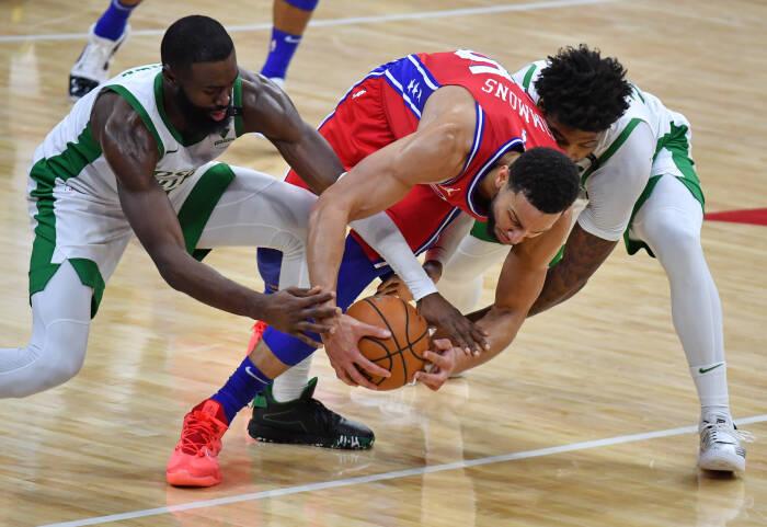 Guard Philadelphia 76ers Ben Simmons (25) berebut bola dengan guard Boston Celtics Jaylen Brown (7) dan guard Marcus Smart (36)