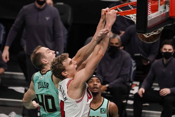 Penyerang Chicago Bulls Lauri Markkanen (24) meraih rim dengan dunk di atas center Charlotte Hornets Cody Zeller (40)