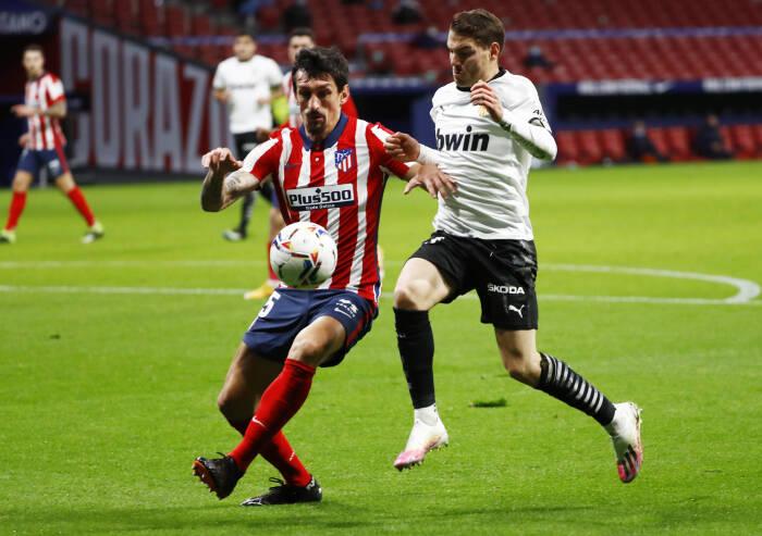 Stefan Savic dari Atletico Madrid beraksi dengan Manu Vallejo dari Valencia