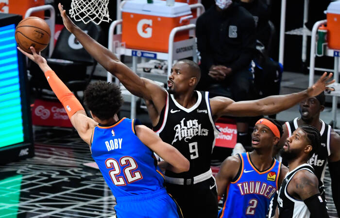 Penyerang Oklahoma City Thunder Isaiah Roby (22) mencoba mencetak angka melewati pemain tengah LA Clippers, Serge Ibaka (9)