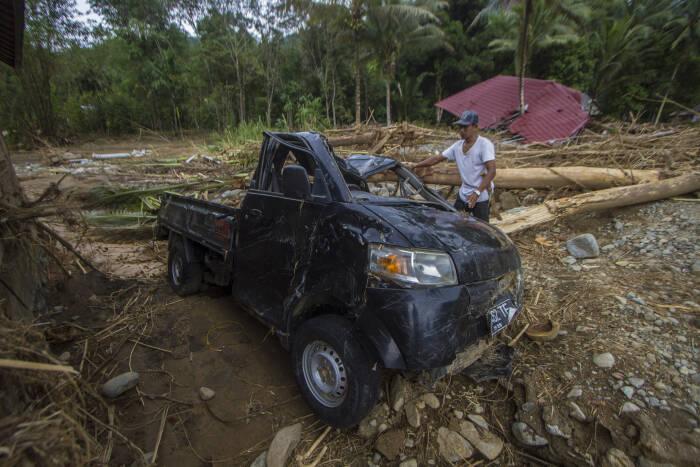 Warga melihat kondisi sebuah mobil yang rusak akibat banjir bandang di Desa Datar Ajab