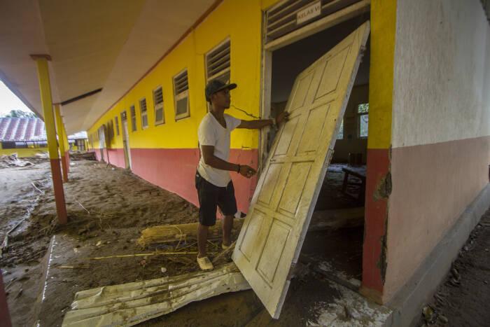 Warga melihat kondisi sebuah bangunan sekolah dasar negeri yang terdampak banjir bandang di Desa Datar Ajab
