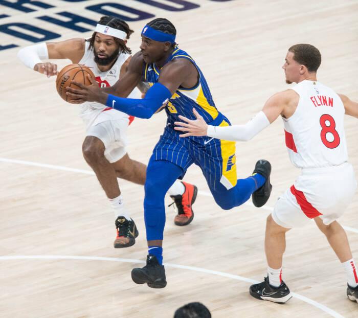 Guard Indiana Pacers Aaron Holiday (3) menggiring bola sementara penyerang Toronto Raptors DeAndre