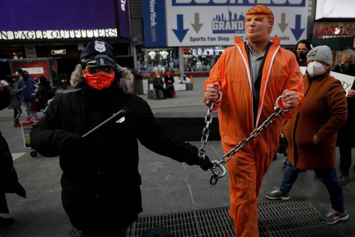 """Seorang demonstran yang mengenakan topeng mantan Presiden AS Donald Trump dinyatakan bersalah selama demonstrasi """"People"""