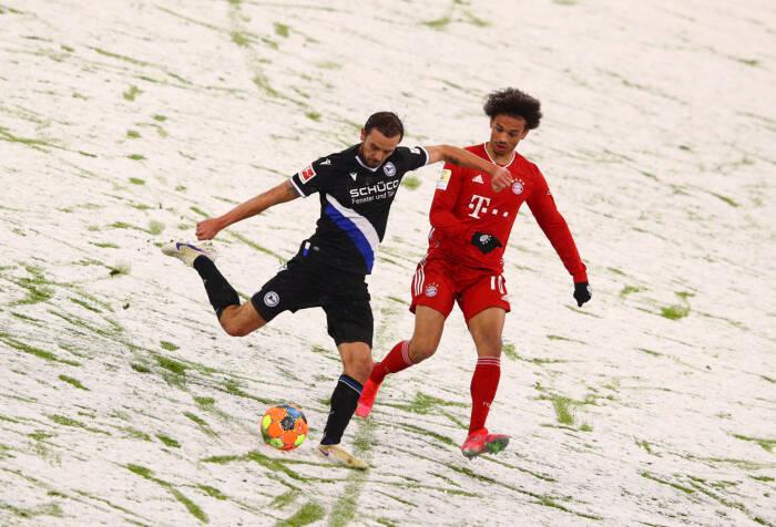Manuel Prietl dari Arminia Bielefeld beraksi dengan Leroy Sane dari Bayern Munich