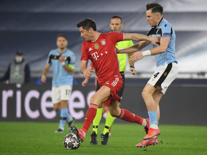Robert Lewandowski dari Bayern Munich beraksi dengan Patric Lazio